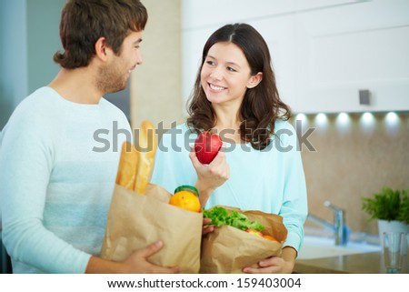 Pretty female and her husband with paper packets in the kitchen - stock photo