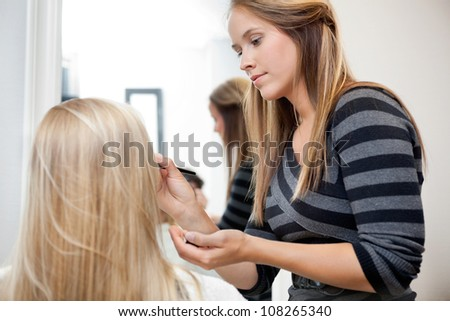 Pretty female artist applying make up to woman in parlor - stock photo
