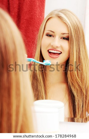 Pretty female brushing her teeth in front of mirror in the morning  - stock photo
