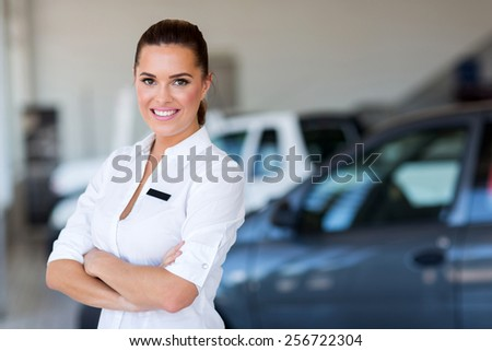pretty female car dealer with arms crossed - stock photo