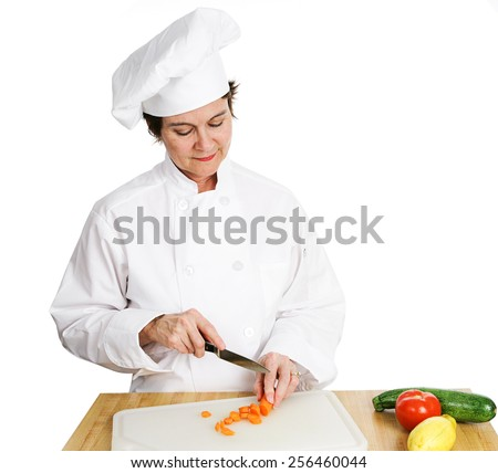 Pretty female chef chopping vegetables on a cutting board.  Isolated on white.   - stock photo