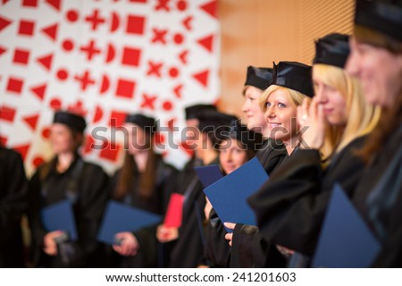 Pretty female college graduate at graduation with classmates, holding their degres. looking happy about their accomplishment
