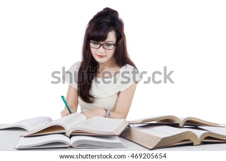 Pretty female college student reading books while writing on the book, isolated on white background