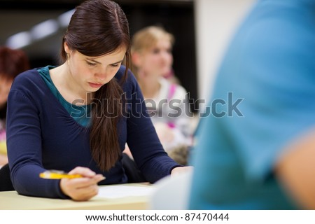 pretty, female college student sitting in a classroom full of students during class (shallow DOF; color toned image) - stock photo