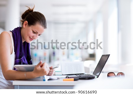 pretty female college student studying in the university library/study room (color toned image) - stock photo