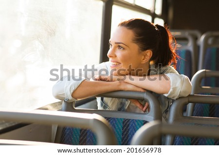pretty female commuter daydreaming on bus - stock photo