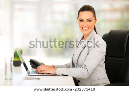 pretty female corporate worker working in office - stock photo