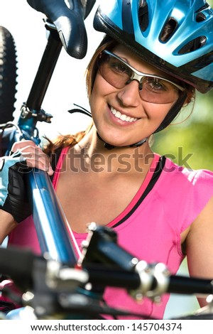Pretty female cyclist carrying her bike on shoulder - stock photo