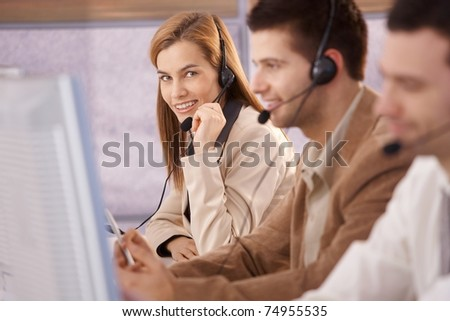 Pretty female dispatcher working in callcenter smiling.? - stock photo