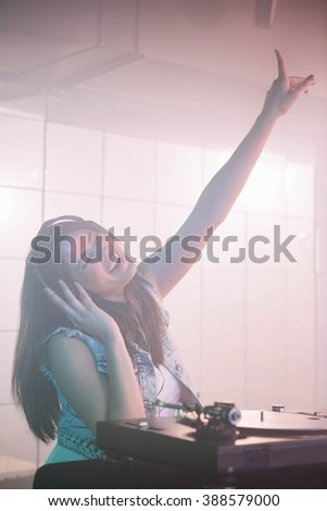 Pretty female DJ waving her hand while listening music at the nightclub