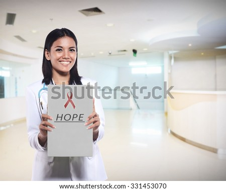 Pretty female doctor show red ribbon on the paper. AIDS awareness concept - stock photo