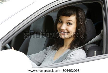 Pretty female driver in a white car - stock photo