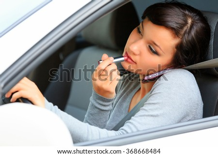 Pretty female driver talking by mobile telephone and doing make-up.