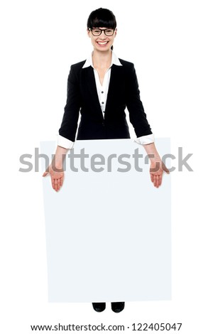 Pretty female executive standing behind blank banner ad isolated against white