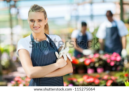 pretty female florist portrait in greenhouse - stock photo