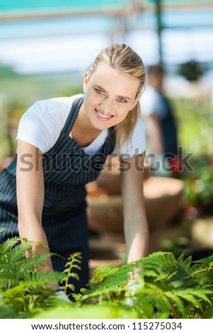 pretty female florist working inside greenhouse - stock photo