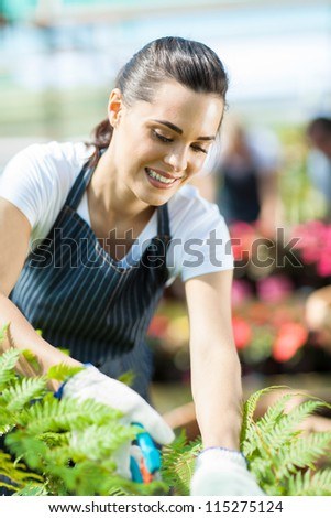 pretty female gardener working inside greenhouse - stock photo
