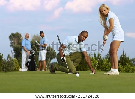 Pretty female golfer learning to putt on the green from male instructor. - stock photo