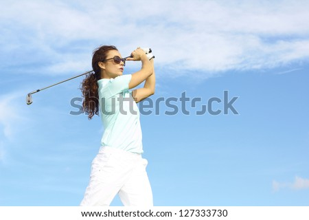 Pretty female golfer taking a golf swing in the rough. - stock photo