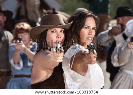 Pretty female gunfighters with pistols at point blank range - stock photo