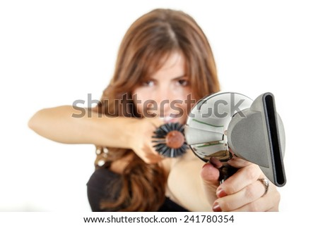 Pretty female hairstylist holding hairdryer and hairbrush pointing at you with focus on hairdryer - stock photo