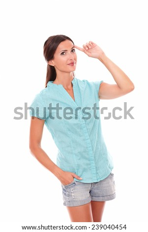 Pretty female in shorts jeans standing and smiling while looking up in white background - copyspace - stock photo