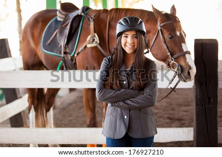 Pretty female Latin jockey wearing a jacket and a helmet standing next to a horse - stock photo