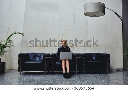 Pretty female looks toward while sitting with open portable net-book in modern studio interior, young woman thinking about new ideas for work in the network while holding on her knees laptop computer - stock photo