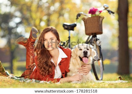 Pretty female lying down with dog in a park - stock photo