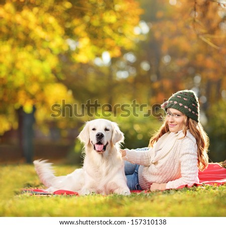 Pretty female lying down with her labrador retriever dog in a park, shot with a tilt and shift lens - stock photo