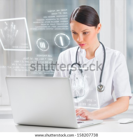 Pretty female medicine doctor working with modern computer interface - stock photo