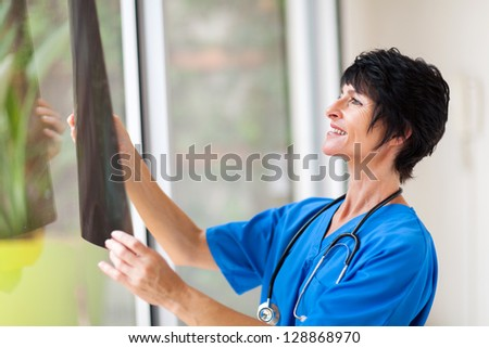 pretty female middle aged medical surgeon looking at x-ray - stock photo