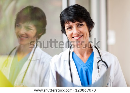 pretty female middle aged medical worker with x-ray standing by window