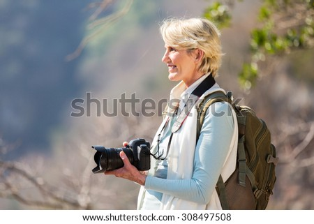 pretty female photographer holding digital camera on top of mountain - stock photo