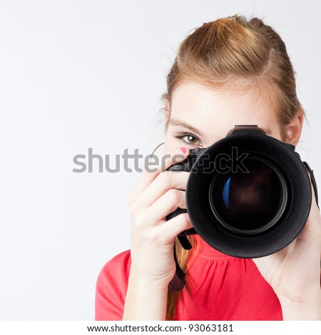 pretty, female photographer with her digital camera (color toned image; shallow DOF) - stock photo