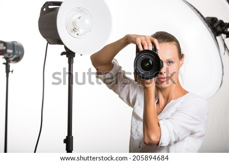 Pretty, female pro photographer with digital camera - DSLR and a huge telephoto lens in her well equiped studio, taking photos (color toned image; shallow DOF) - stock photo