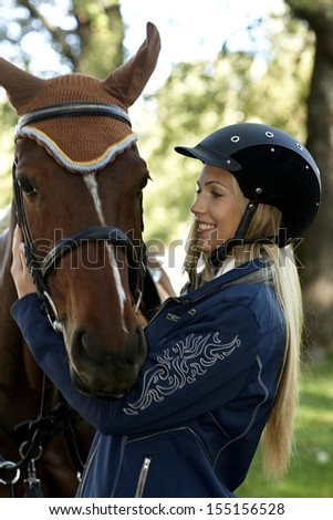 Pretty female rider embracing horse outdoors. - stock photo