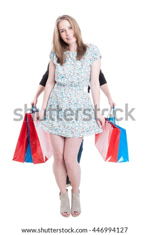 Pretty female shopper and male behind her carrying shopping bags isolated on white background