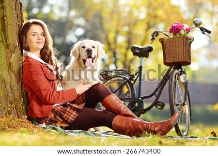 Pretty female sitting down with her labrador retriever dog in a park and looking at camera - stock photo