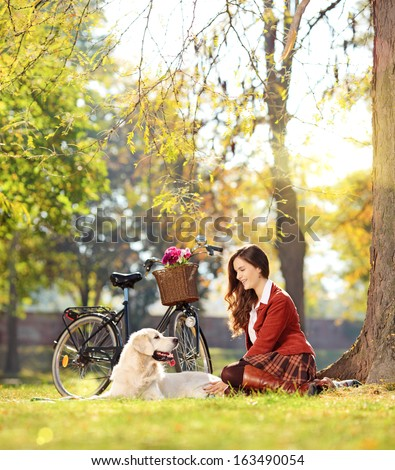 Pretty female sitting down with her labrador retriever dog in a park, shot with a tilt and shift lens - stock photo