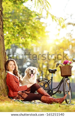 Pretty female sitting on a grass with her labrador retriever dog and looking at camera in a park  - stock photo