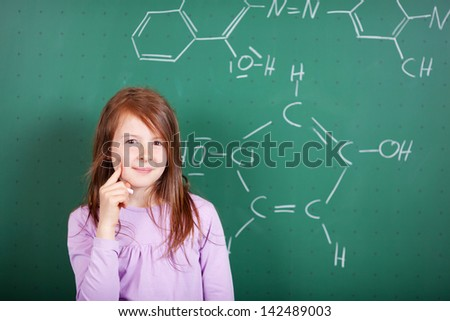 Pretty female student puzzling a chemistry question standing against a blackboard with a drawing of a chemical formula with a thoughtful expression