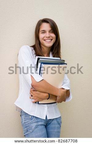 Pretty female student standing against a wall with books in her hands
