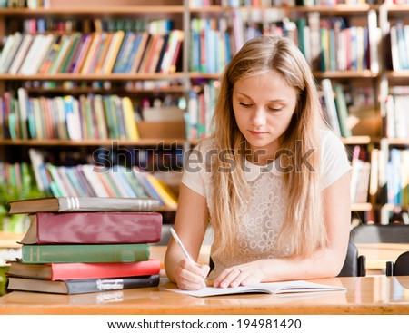 pretty female student with books working in a high school library - stock photo