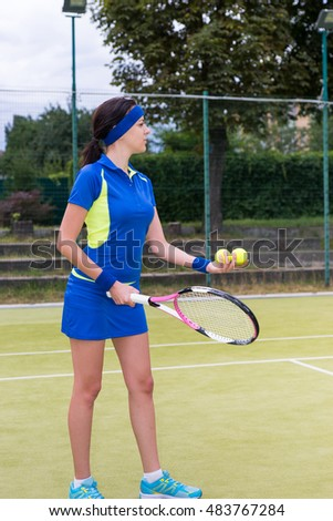 Pretty female tennis player preparing to serve wearing a sportswear during a match on a court outdoor in summer or spring