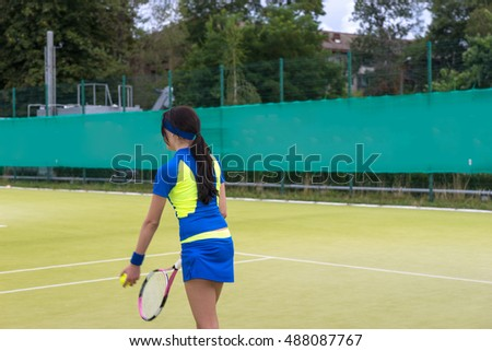 Pretty female tennis player wearing a sportswear warming up before tennis match on a court outdoor in summer or spring