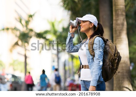 pretty female traveler taking photos in the city - stock photo