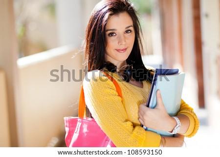 pretty female university student holding books - stock photo
