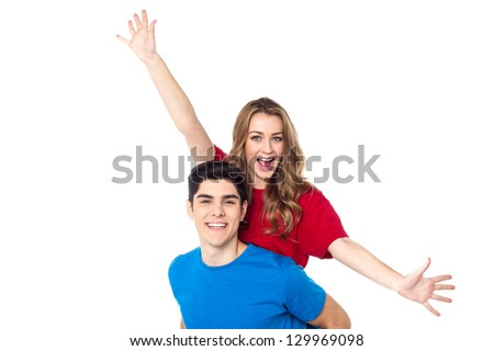 Pretty female with her arms outstretched enjoying piggyback ride. - stock photo