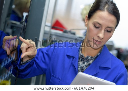 pretty female worker using digital tablet in manufacturing industry